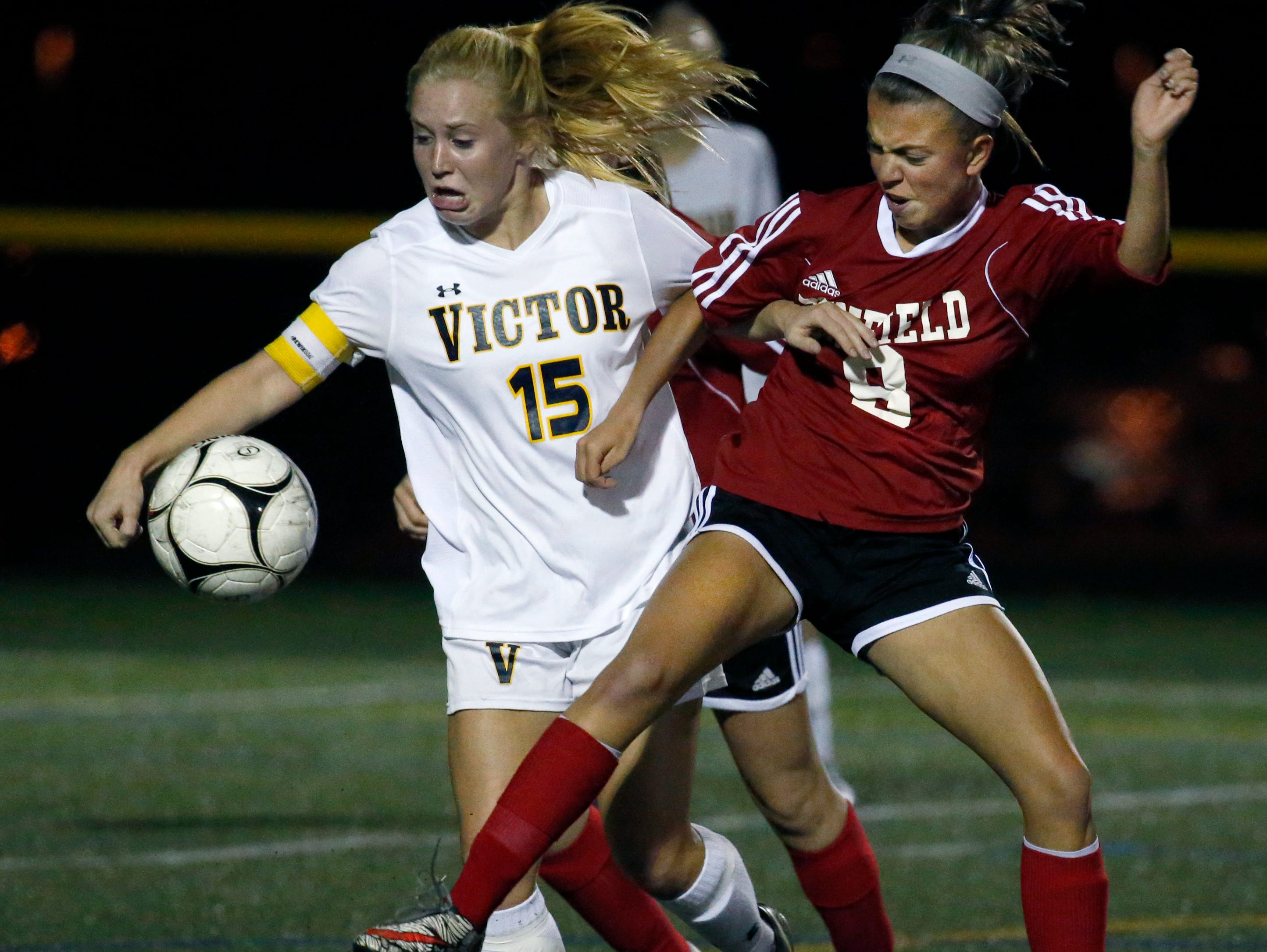 Victor's Kaci Messier and Penfield's Kinsey Uzalec in the first half at Webster Schroeder High School.