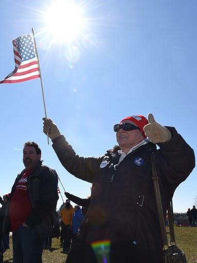 Waving an American flag, Linda Ann isaacson, of Westland,