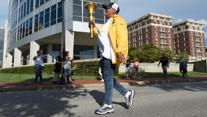 Lu porter walks the last leg of the day for the Indiana Bicentennial Torch Relay along Riverside Drive in downtown Evansville Saturday.  The torch is traveling 3200 miles through each of the 92 counties in Indiana before arriving in Marion County in October.