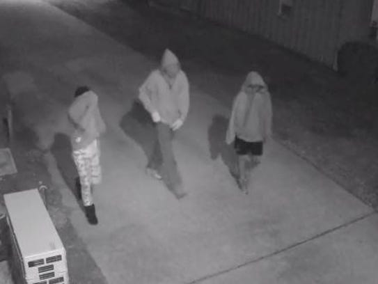 What appear to be three youths cover their faces as