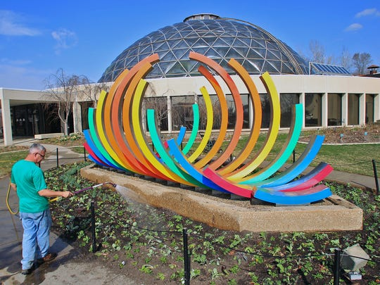 """Des Moines Botanical Garden employee Todd Monson waters about 5,000 plants that went into the ground over two days in March 2012 near the """"Spectral Liberation"""" spulpture."""