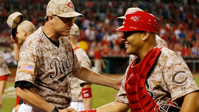 Reds manager Bryan Price and catcher Brayan Pena celebrate Wednesday's 5-0 win against the Los Angeles Dodgers at GABP.