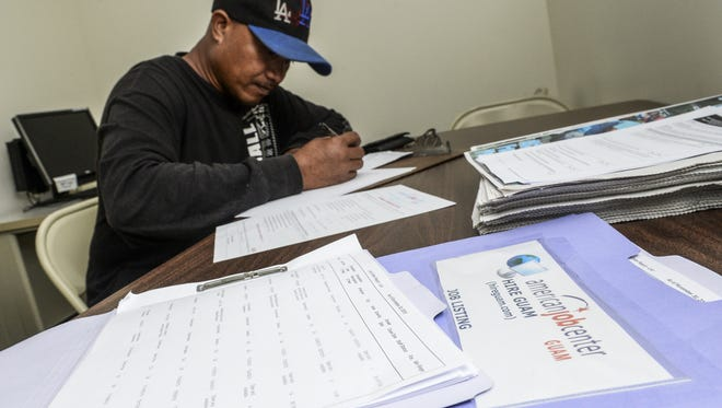 Dededo resident Joe Galtutuw, 36, fills out an employment application at the Department of Labor's American Job Center Guam in Hagatna, as he seeks assistance in finding a job on Wednesday, Dec. 2.