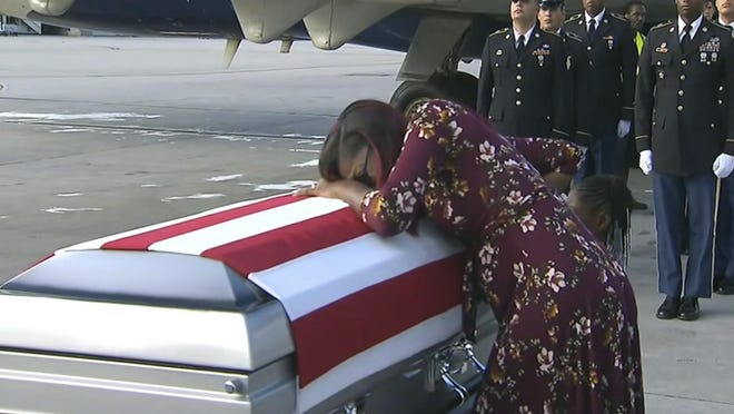 """Myeshia Johnson cries over the casket of her husband, Sgt. La David Johnson. WPLG via AP ADDS TRUMP'S RESPONSE TO REP. WILSON - In this Tuesday, Oct. 17, 2017, frame from video, Myeshia Johnson cries over the casket of her husband, Sgt. La David Johnson, who was killed in an ambush in Niger, upon his body's arrival in Miami. President Donald Trump told the widow that her husband """"knew what he signed up for,"""" according to Rep. Frederica Wilson, who said she heard part of the conversation on speakerphone. In a Wednesday morning tweet, Trump said Wilson's description of the call was """"fabricated."""" (WPLG via AP)"""