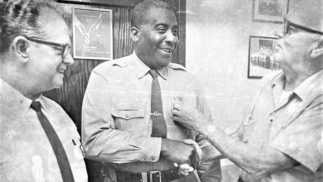 Oliver (center) is congratulated on his promotion in 1969 by businessman John Murray (right) and Police Chief Broadus Bequest.