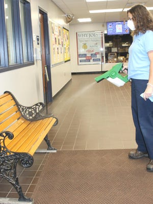 Tammy Walker, head custodian of BACC, using an electrostatic disinfectant sprayer in the entrance of the building and on frequently-touched areas.