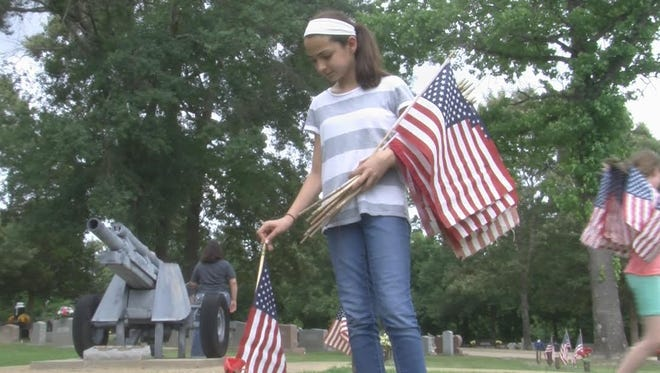 A troop of Texas Girl Scouts place American flags on veterans' graves.