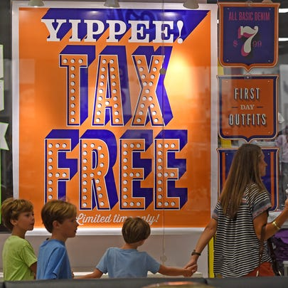 Customers pass by signs  advertising a tax-free weekend