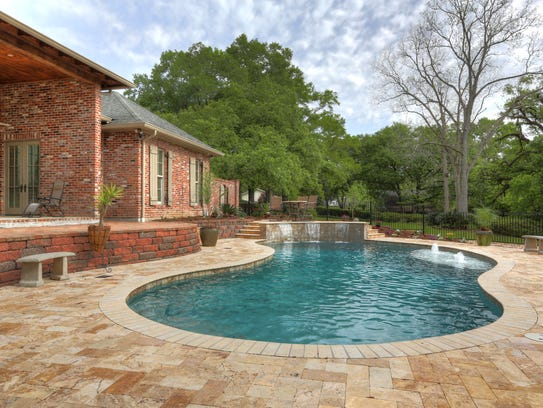 The pool and spa are surrounded by brick decking and