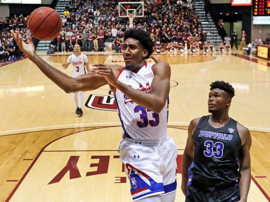 Southern Illinois' Kavion Pippen, left, loses control of the ball on his way to the basket as Buffalo's Nick Perkins watches during the second half of an NCAA college basketball game Monday, Nov. 12, 2018, in Carbondale, Ill. Buffalo won 62-53. (AP Photo/Jeff Roberson)