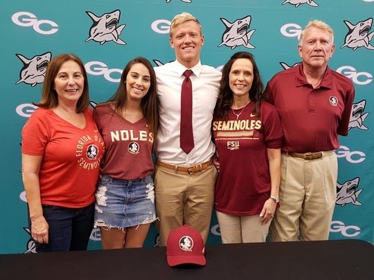 Gulf Coast High School senior Cole Gutknecht (center) poses with his family after committing to swim at Florida State at a signing ceremony Wednesday, April 11, 2018.