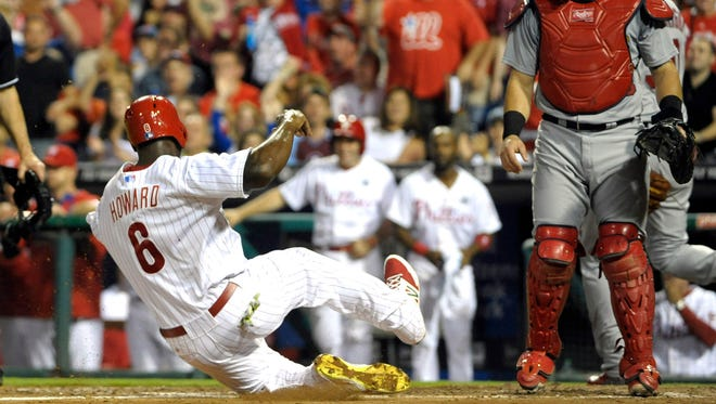 The Phillies' Ryan Howard scores a run on throwing error in the third inning Friday.