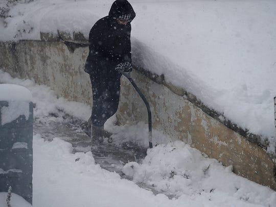 Kim Hoag digs out her driveway after a record amount