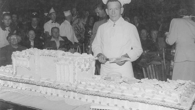 Master Baker Bill Hammontree of the Phoenix Post House shows off his creation, a cake for the opening of the Phoenix Greyhound Bus Terminal.