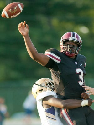 A male defensive player wraps up Ballard quarterback Terrance May as May tries to unload the ball.25 August 2017