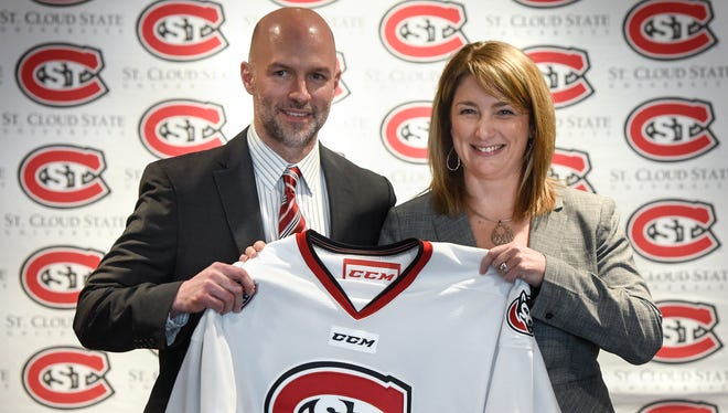 New St. Cloud State University men's hockey coach Brett Larson holds a hockey jersey with athletic director Heather Weems during a press conference Friday, April 13, at the Herb Brooks National Hockey Center in St. Cloud.