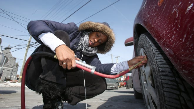 Kurtisa Shaw of Dobbs Ferry puts air in her tires at a local service station Monday.