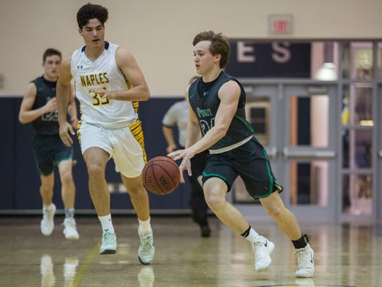 Brady Luttrell drives to the hoop during the Class 7A regional quarterfinal game at Naples High School on Thursday, Feb. 22, 2018.