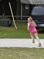 A youngster chases after a foul ball hit over the backstop
