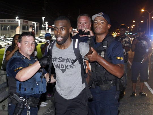 Police arrest activist DeRay McKesson during a protest along Airline Highway, a major road that passes in front of the Baton Rouge Police Department headquarters Saturday in Baton Rouge, La.