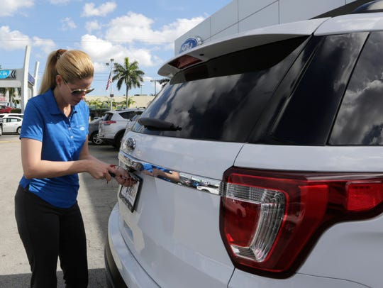Ford sales consultant Yanaisis Milian removes the dealer