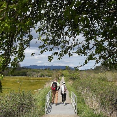 Hikers on the River Estuary Trail  at the Theler Wetlands