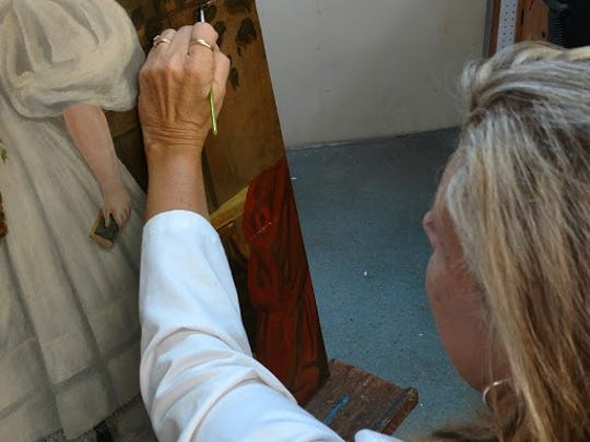 Freda Nicholas is shown in her workshop bringing new life to old paintings.
