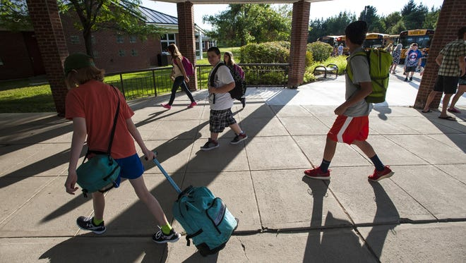 Students stream through the front door on the first day of classes at Williston Central School on Wednesday, August 26. The Williston School Board is straining to find more than $700,000 in budget savings to avoid a double tax penalty under the state's new education law, Act 46.