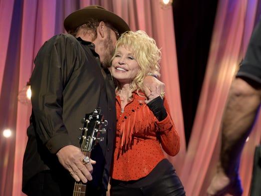 Hank Williams Jr. hugs Dolly Parton at the pre-taping
