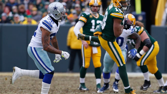 Green Bay Packers wide receiver Randall Cobb (18) catches a pass from Green Bay Packers quarterback Aaron Rodgers during the first half of an NFL divisional playoff football game against the Dallas Cowboys Sunday, Jan. 11, 2015, in Green Bay, Wis. (AP Photo/Mike Roemer)