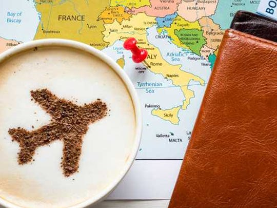 A travel airplane in a cappuccino on top of a map,tickets,