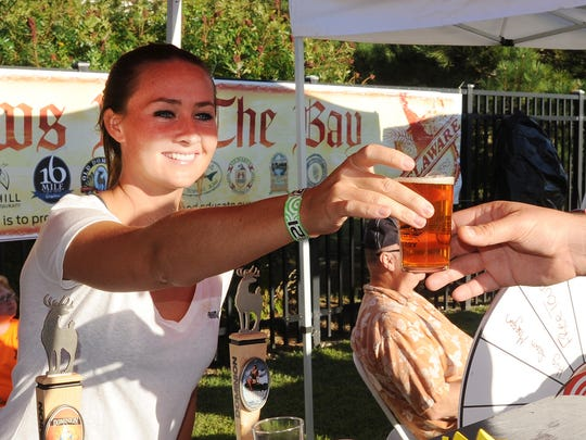 Brittany Thomas from Dover's Fordham & Dominion Brewing Company serves a sample at Brew by the Bay in 2013, the first year the festival also included New Jersey brewers.