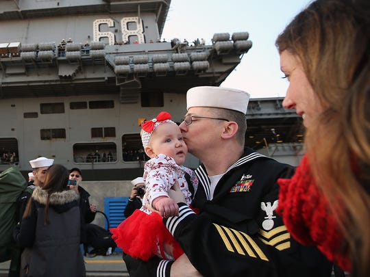 USS Nimitz sailor Adam Harrelson kisses 6 month-old daughter Savannah after being greeted by his wife Rachel on the pier at Naval Base Kitsap-Bremerton on Sunday, December 10, 2017. Savannah was born the day the aircraft carrier deployed.