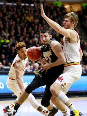 Maryland guard Melo Trimble, left, knocks the ball away from Purdue guard Dakota Mathias while Maryland forward Jake Layman, right, defends Mathias in the Boilers' win Saturday.
