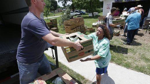 Jason Goedde, a driver with Ozarks Food Harvest, hands off a box of produce to volunteer Barbara Vergason at the Grant Beach Community Garden food distribution site.