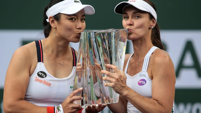 Hung-Jan Chan, of Taiwan, and Martina Hingis, of Switzerland, kiss their BNP Paribas Open women's doubles trophy after beating Czech Republic players Lucie Hradecka and Katrina Siniakova in the finals on Saturday, March 18, 2017 in Indian Wells, CA.