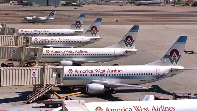 America West airplanes fill their loading ramp as another takes to the skies in 1992 at Sky Harbor airport in Phoenix, Ariz.