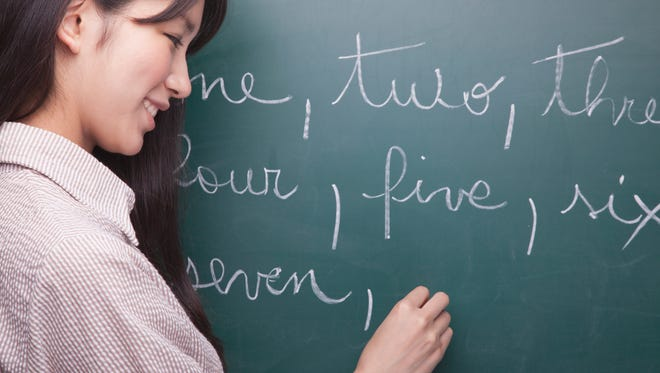 Young woman student writing English numbers on blackboard.