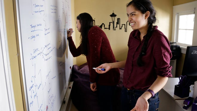 Aishwarya Mandyam, left, and her twin sister, Karishma Mandyam, write on an idea board for an upcoming hack-athon in the 3,100-square-foot home they share rent-free with six other University of Washington computer science and technology students in Seattle on Sept. 29, 2015 .