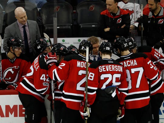 Devils head coach John Hynes, top left, looks on as assistant coach Geoff Ward talks to players during the third period of a game against the Carolina Hurricanes, Saturday, March 25, 2017, in Newark, N.J. The Hurricanes won 3-1. (AP Photo/Julio Cortez)