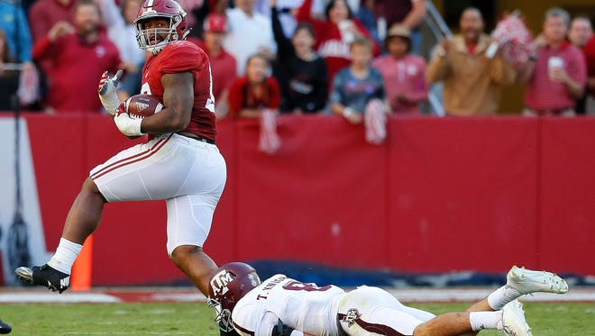 Alabama's Jonathan Allen  returns a fumble for a touchdown as he steps over Texas A&M's Trevor Knight in a game last season.
