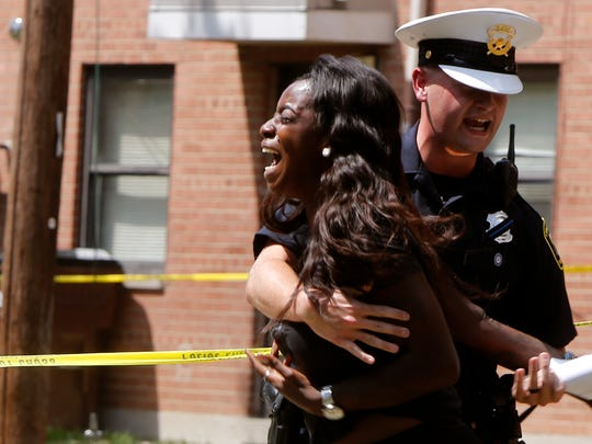 """A woman screams, """"That's my brother,"""" at the scene of a fatal shooting in the West End on July 23."""