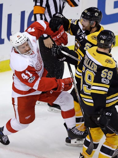 Red Wings center Luke Glendening (41) is checked by