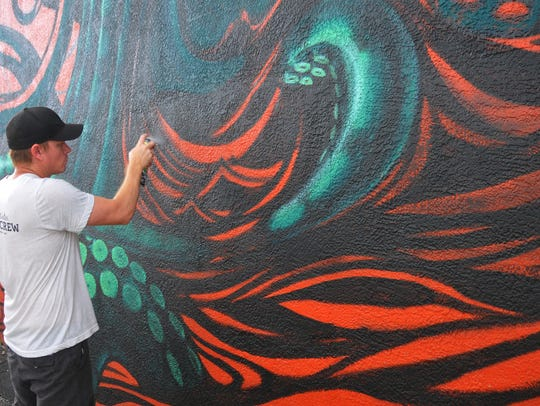 Ian Soden works on his giant octopus mural on the east wall of Intracoastal Brewing Co. last fall during the Anti-Gravity Project.