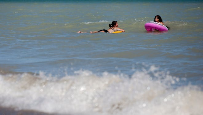 Two people float on tubes over waves on Lake Huron August 28, 2014 at Lakeport State Park in Burtchville Township.