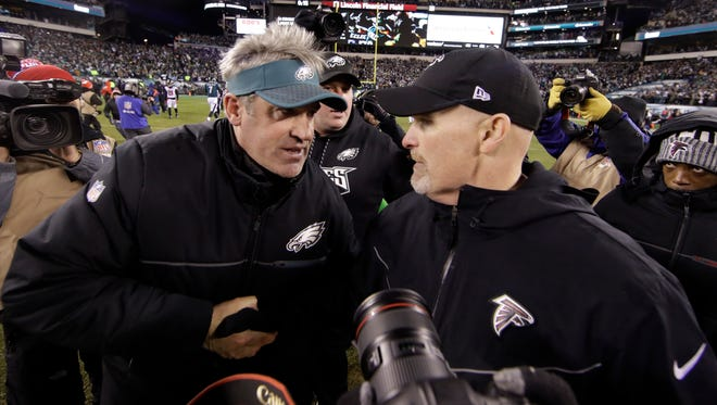 Philadelphia Eagles head coach Doug Pederson, left, and Atlanta Falcons head coach Dan Quinn meet after an NFL divisional playoff football game, Saturday, Jan. 13, 2018, in Philadelphia. Philadelphia won 15-10.