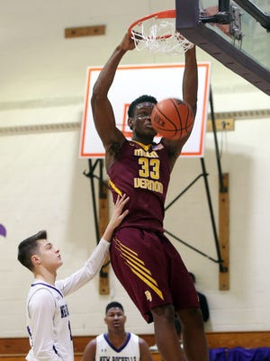 Mt. Vernon's  Gregory Calixthe (33) dunks in front of New Rochelle's Jayson Rodopoulos (24) during boys basketball action at New Rochelle High School Jan. 21, 2017. Mt. Vernon won the game 71-46.