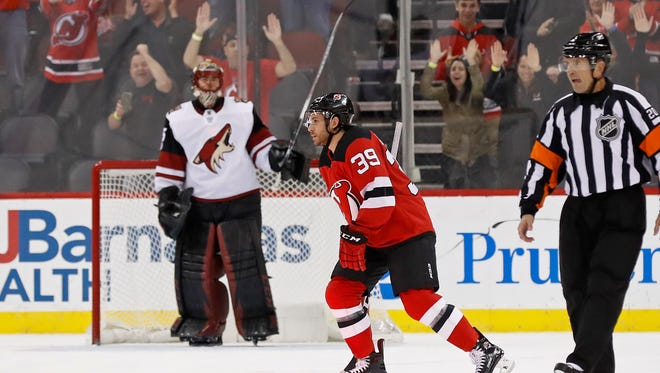 New Jersey Devils' Brian Gibbons (39) skates past Arizona Coyotes goalie Louis Domingue after scoring a penalty shot goal during the first period of an NHL hockey game Saturday, Oct. 28, 2017, in Newark, N.J.