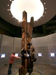 """ADVANCE FOR USE SUNDAY, SEPT. 11, 2016 AND THEREAFTER-FILE - In this Friday, Sept. 11, 2015 file photo, Landon Cole reaches out to touch steel beams from the World Trade Center on display at the The George W. Bush Presidential Library and Museum in Dallas. """"They are the relics of the destruction and they have the same power in the same way as medieval relics that have the power of the saints,"""" said Harriet Senie, a professor of art history at the City University of New York and author of """"Memorials to Shattered Myths: Vietnam to 9/11."""" (AP Photo/LM Otero)"""