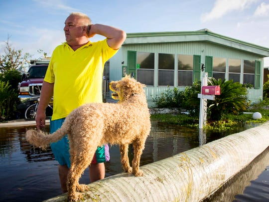 Charles Pulkownik, 56,  and his dog Cesar rode out the storm at their home in Naples Estates trailer park in East Naples Monday, Sept. 11, 2017, and are cleaning up after Hurricane Irma passed through Southwest Florida.